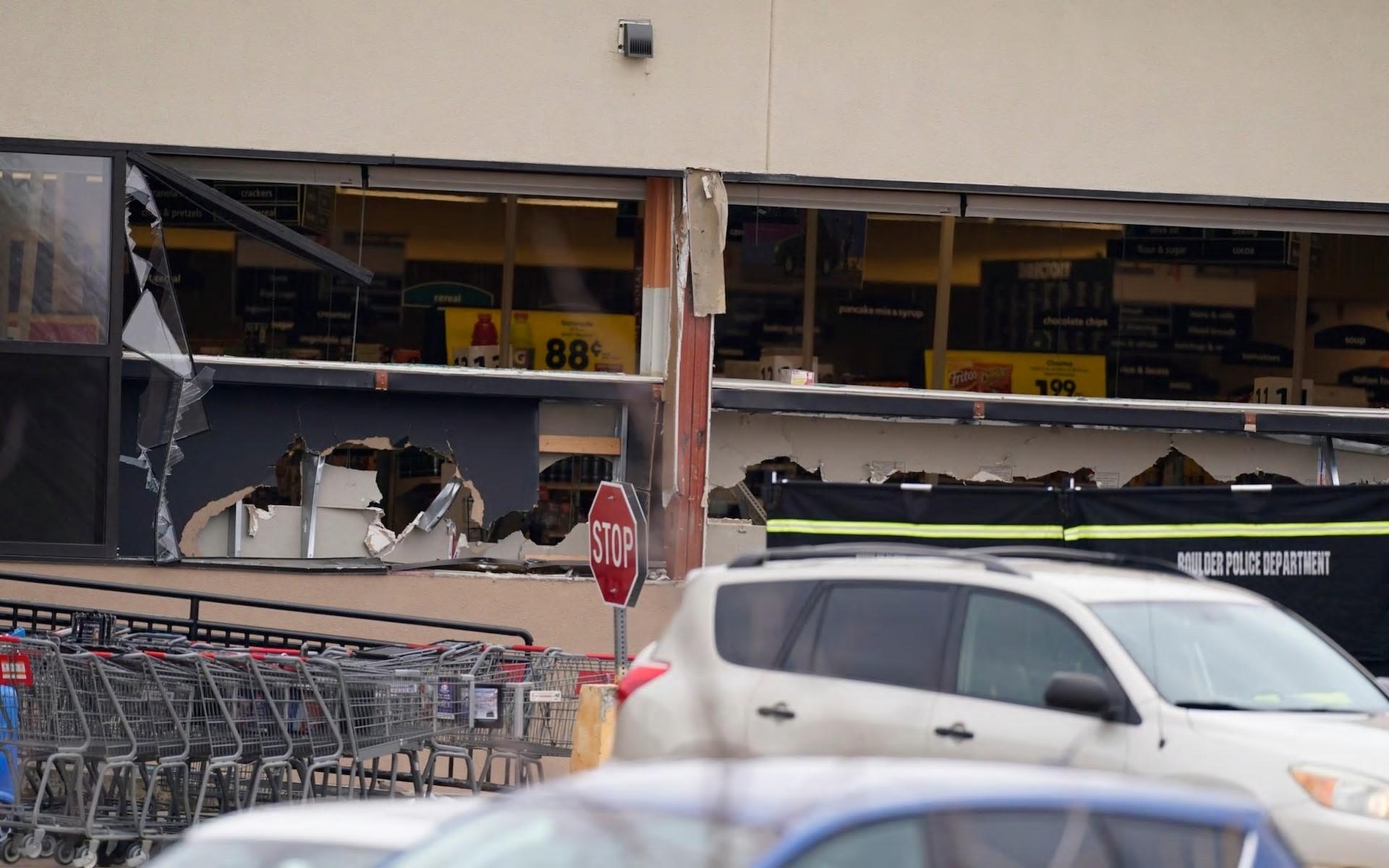 停在建筑物侧面的汽车:商店外面的窗户损坏-AP
